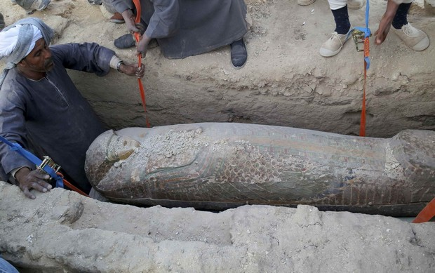 A wooden sarcophagus is lifted from the ground in Luxor