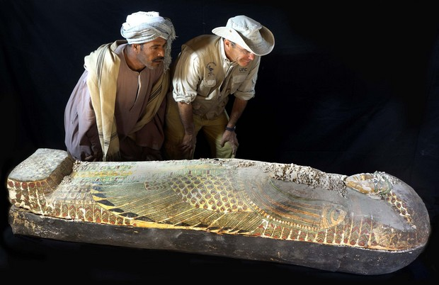 An archaeologist and a Egyptian worker look at a wooden sarcophagus that was lifted from the ground in Luxor, southern Egypt